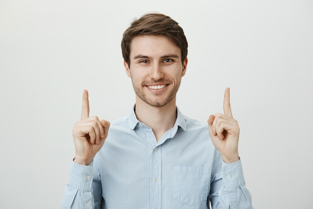 Handsome confident businessman pointing fingers up