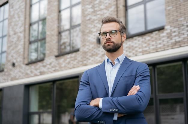 スタートアップを計画しているスーツの眼鏡を身に着けているハンサムな自信を持ってビジネスマン成功したビジネス