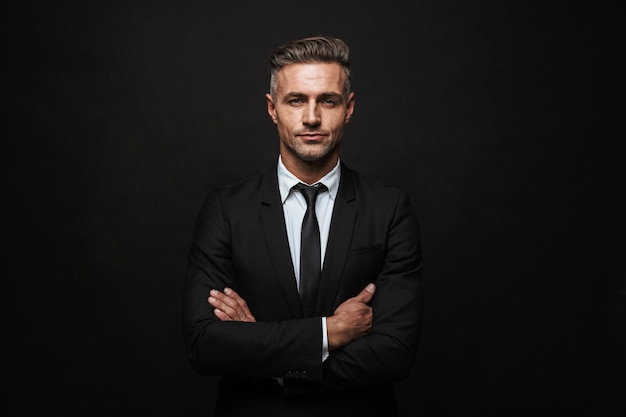 Handsome confident businessman wearing suit standing isolated over black wall, arms folded