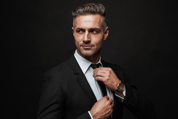 Handsome confident businessman wearing suit standing isolated over black wall, posing