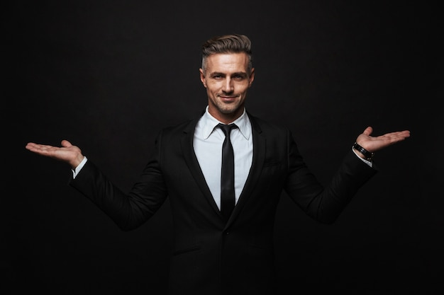 Handsome confident businessman wearing suit standing isolated over black wall, presenting copy space