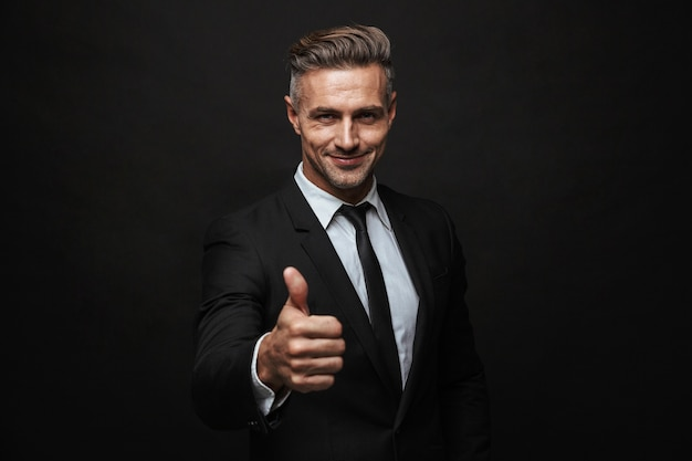 Handsome confident businessman wearing suit standing isolated over black wall, thumbs up