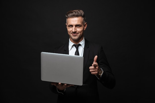 Handsome confident businessman wearing suit standing isolated over black wall, working on laptop computer, pointing finger at camera