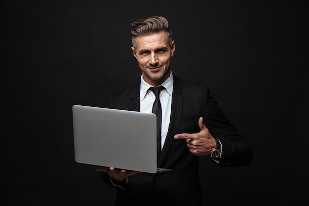 Handsome confident businessman wearing suit standing isolated over black wall, working on laptop computer, pointing