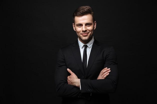 Красивый уверенный бизнесмен в костюме, стоящий изолированно над черной стеной, скрестив руки на груди