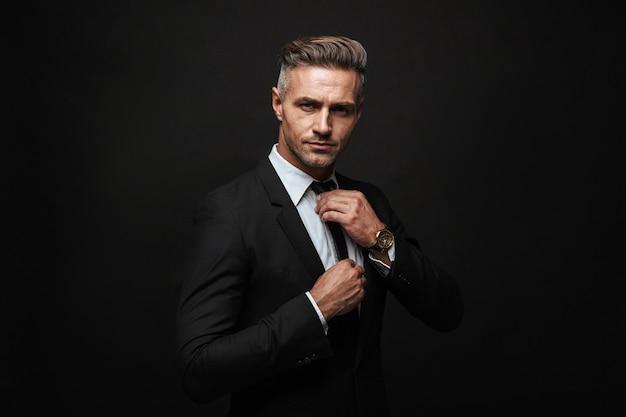 Красивый уверенный бизнесмен в костюме, стоящий изолированно над черной стеной, позирует