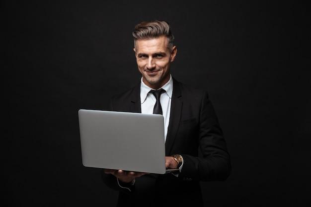 Красивый уверенный бизнесмен в костюме, стоящий изолированно над черной стеной, работая на портативном компьютере