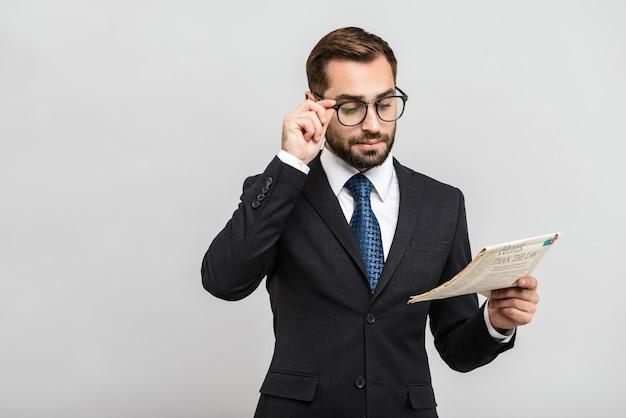 Красивый уверенный бизнесмен в костюме, стоящий изолированно над серой стеной, читая газету, в очках