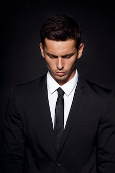 Handsome confident businessman with his head bowed wearing suit standing isolated on black
