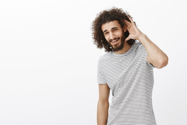 Handsome confident easter male model with curly hairstyle and beard, bending head and holding hand on ear, smiling broadly
