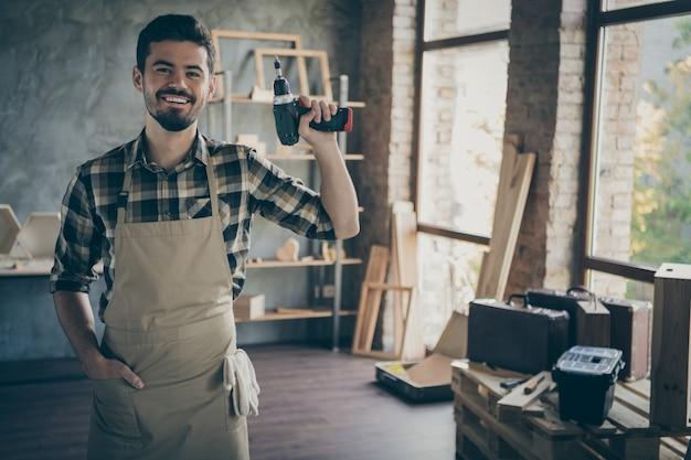 Красивый уверенный в себе парень мастер держит электрическую беспроводную дрель дружелюбно улыбается готов начать ремонт собственный деревянный бизнес студия столярный цех гараж в помещении