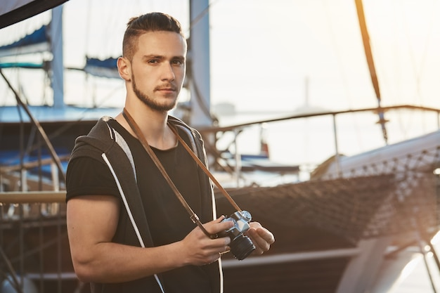 Handsome confident guy with stylish haircut standing near awesome yacht, holding camera, staring seriously and being focused during photo session in harbour, making pictures of scenery