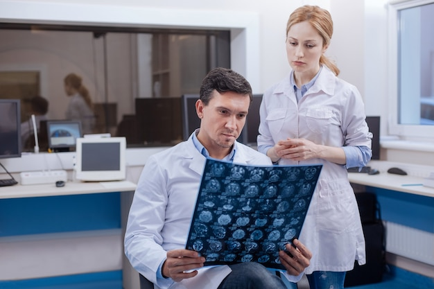 Handsome confident male oncologist sitting near his female colleague and examining the radiograph