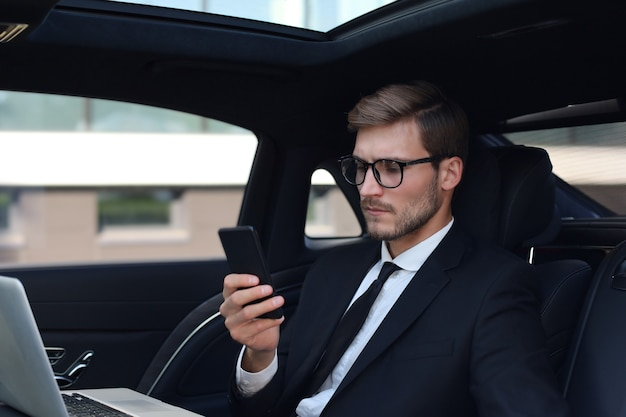 Handsome confident man in full suit looking at his smart phone while sitting in the car and using laptop.
