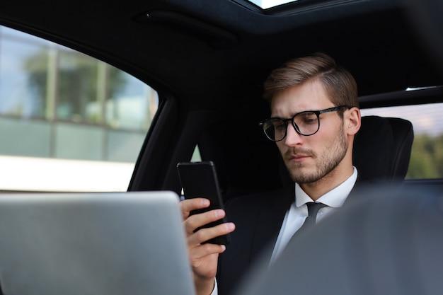 車に座ってラップトップを使用しながら彼のスマートフォンを見て完全なスーツを着たハンサムな自信のある男。