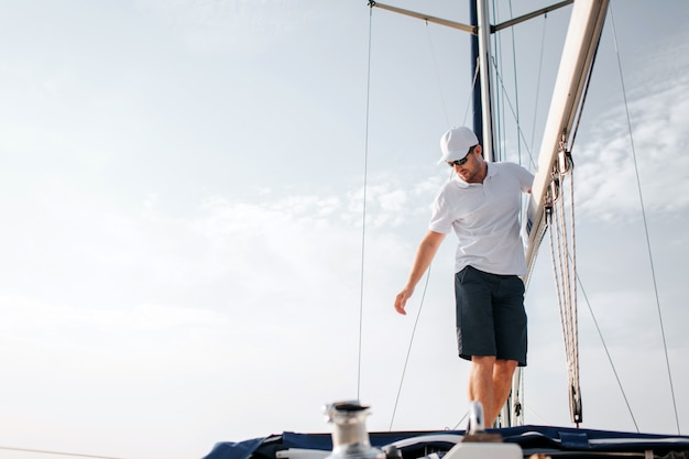 Handsome and confident man stands on yacht board and holds on big mast. he looks down and reaches with hand. young man is serious and concentrated. he poses.
