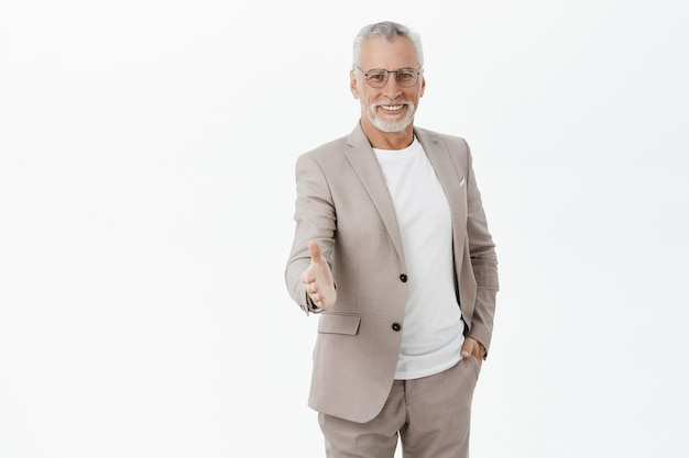 Handsome confident old male entrepreneur extend hand for handshake, greet business partner