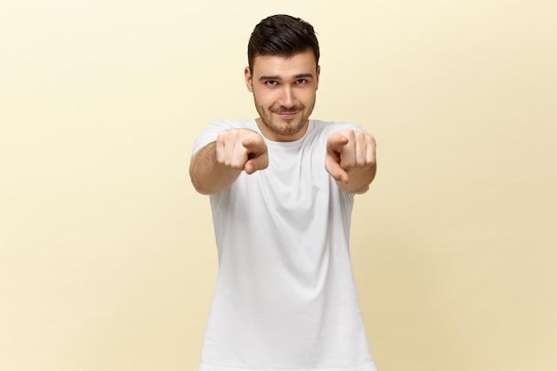 正面を向いている白いカジュアルなtシャツでハンサムな自信を持ってポジティブな若い男