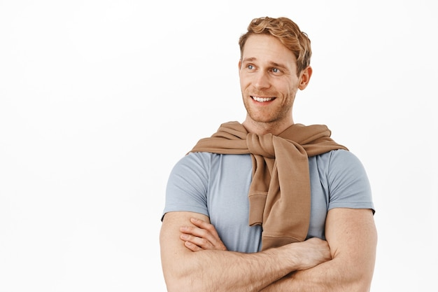 Handsome and confident redhead man cross arms on chest, showing fit perfect body with strong arms, looking left and smiling like professional, standing over white wall