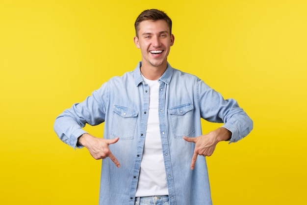 Handsome confident smiling man in casual outfit, pointing fingers down as showing advertisement, recommend click banner, special offer in store, standing yellow background happy.