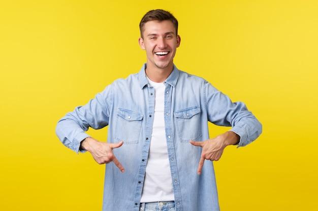 캐주얼 복장을 한 잘생긴 자신감 넘치는 웃는 남자, 광고를 보여주는 것처럼 손가락을 아래로 가리키고, 클릭 배너를 추천하고, 상점에서 특별 제안을 하고, 노란색 배경을 행복하게 서 있습니다.