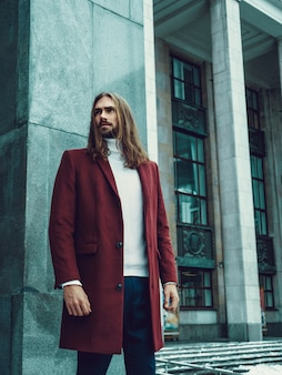Handsome confident well dressed man with beard posing outdoors looking away. fashionable rich male model in red winter coat and white sweater