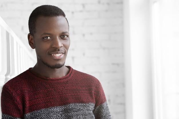 カジュアルな暖かいセーターを着たハンサムな自信を持って若いアフリカ系アメリカ人