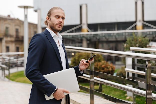 Красивый уверенный молодой бородатый бизнесмен, стоящий на улице на улице, используя мобильный телефон, неся ноутбук