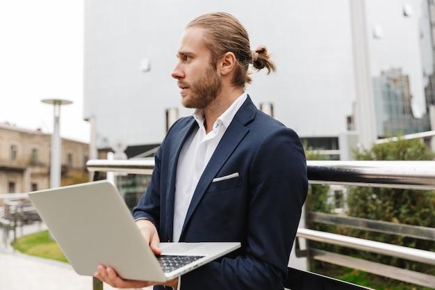 Красивый уверенно молодой бородатый бизнесмен, стоящий на открытом воздухе на улице, работая на портативном компьютере