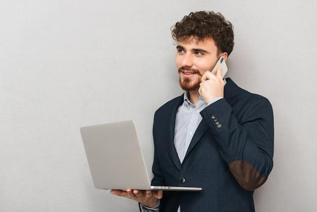 Красивый уверенный молодой бизнесмен в куртке, стоящей изолированно над серым, работая на портативном компьютере, разговаривая по мобильному телефону