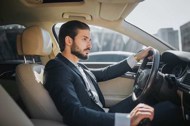 Handsome and confident young man sits in car and looks straight forward. he drives car. it looks luxury inside. he holds one hand on steering wheel and another one on handbrake.