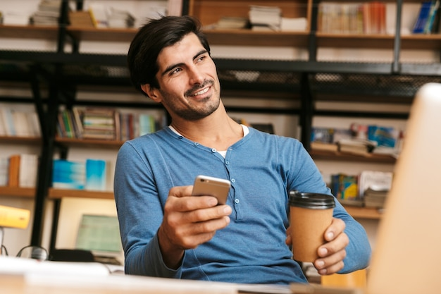 Handsome confident young man sitting at the library desk, working/studying, using laptop computer, holding mobile phone, drinking coffee