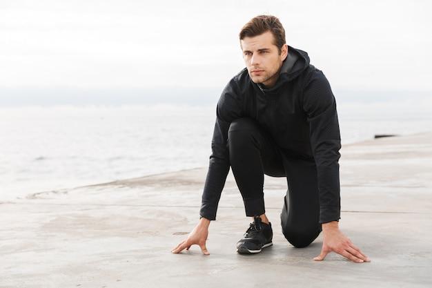 ハンサムな自信を持って若いスポーツマンがビーチで運動し、走り始める準備ができて、ポーズをとる