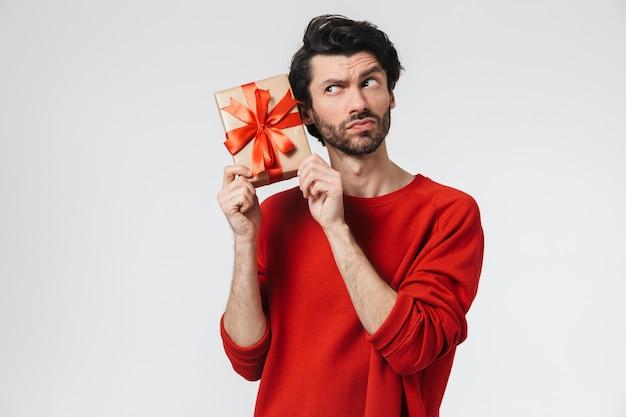 Красивый сбитый с толку молодой бородатый брюнет в свитере стоит над белой и держит подарочную коробку