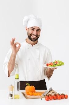 白い壁の上に分離された野菜サラダとおいしいサインと保持プレートを示す制服を着たハンサムな料理人