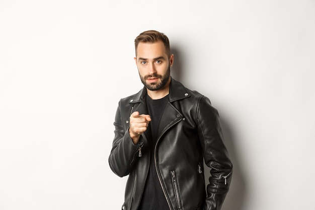 Handsome and cool bearded guy pointing finger at camera, wearing leather jacket, standing sassy