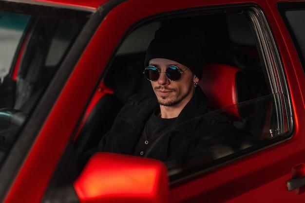 모자와 선글라스를 쓴 검은색 재킷을 입은 멋진 남자가 빨간 차를 운전합니다. 자동차로 여행