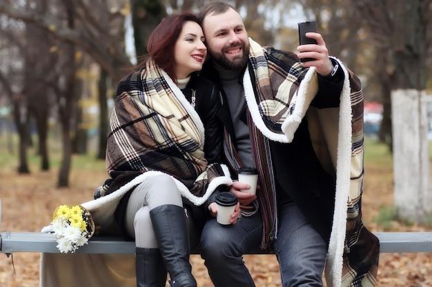 秋の公園で花と恋にデートのハンサムなカップル