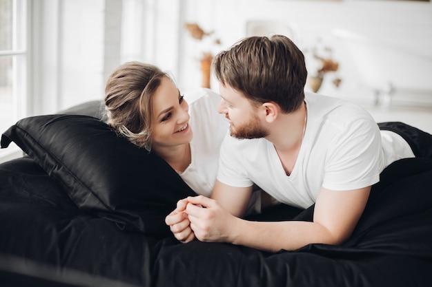 恋にハンサムなカップルは一緒に多くの自由な時間を過ごし、黒いソファに横になります