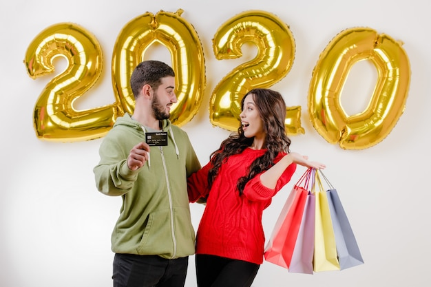 Handsome couple man and woman holding credit card and colorful shopping bags in front of 2020 balloons