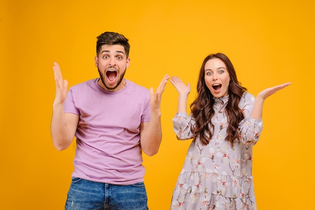 Handsome couple man and woman surprised and screaming isolated