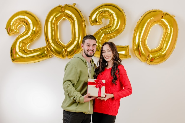 Handsome couple man and woman with christmas present in front of 2020 new year balloons