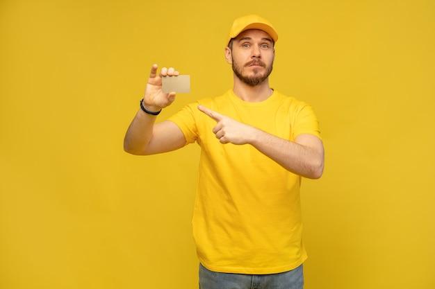黄色の壁に名刺とハンサムな宅配便 Premium写真