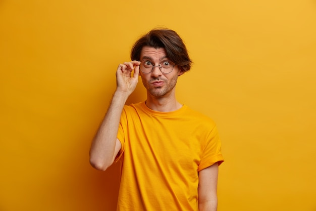 Handsome curious man looks attentively through glasses, has attentive gaze, dressed in casual clothing, has scrupulous look, isolated on yellow wall, gets interesting suggestion