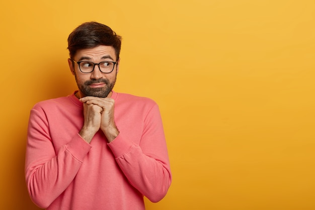 Handsome curious man looks right on empty yellow space, keeps hands under chin, considers buying something, has interest, wears spectacles and rosy jumper, poses indoor, anticipates event happen