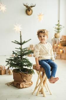 Красивый кудрявый мальчик украсил елку в белой комнате