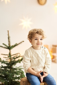 A handsome curly little boy sits on a wooden chair near a christmas tree in a white room