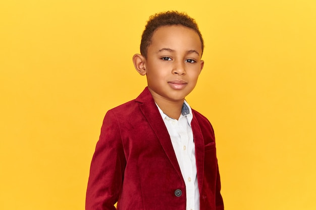 Handsome cute african american little posing isolated having confident facial expression, smiling, wearing trendy crimson velvet jacket.