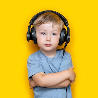 Handsome cute blonde little boy three years old in gaming black headphones