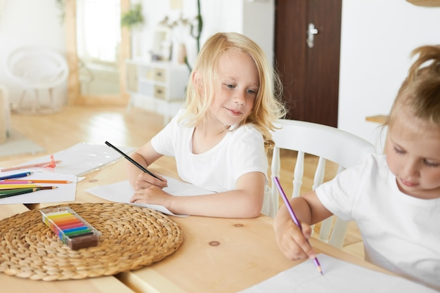 Handsome cute schoolboy with loose blond hair holding pencil having curious facial expression, looking at his baby sister who is sitting next to him, drawing something on blank white sheet of paper